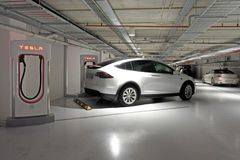 Tesla plug-in electric car Model X been charged by a Supercharge Stock Photo
