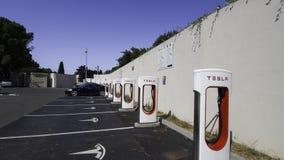 Tesla pojazdy ładuje przy Supercharger słupami fotografia royalty free
