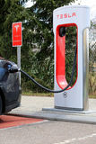 Tesla Supercharger with Black Tesla Car Charging Royalty Free Stock Photo