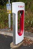 Tesla Supercharger and sign. SARN, UNITED KINGDOM - AUGUST 2, 2018 : A Tesla Supercharger and parking sign at the Sarn Park motorway services off the M4 near royalty free stock image