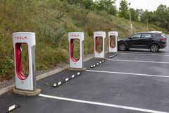 Tesla Superchargers in car park. SARN, UNITED KINGDOM - AUGUST 2, 2018 : A row of Tesla Superchargers next to empty parking bays at the Sarn Park motorway stock photography