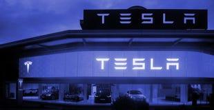 Tesla viaja en automóvili la sala de exposición con los coches dentro de y el salvado iluminado del logotipo fotos de archivo