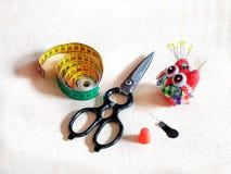 Tesouras, almofada de alfinetes, agulhas, dedal, centímetro Fotografia de Stock Royalty Free
