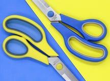 Tesouras amarelas e azuis, contra um fundo colocado liso de contraste imagens de stock royalty free