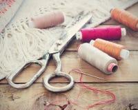 Tesouras, bobinas com linha e agulhas, tela listrada Ferramentas velhas da costura no fundo de madeira velho vintage Foto de Stock Royalty Free