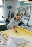 Tesouras de Cutting Fabric With do alfaiate na oficina fotos de stock