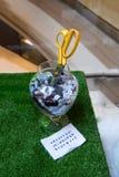 Tesouras e parte inferior postas na garrafa de vidro Fotos de Stock