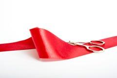 Tesouras e uma fita vermelha Fotografia de Stock