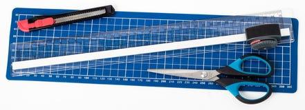 Tesouras, faca de papel em um fundo branco Fotos de Stock Royalty Free