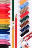 Tesouras, lápis e botões vermelhos em zíperes coloridos em cores diferentes Imagens de Stock