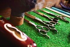 Tesouras para cortar em uma esteira verde no barbeiro Imagem de Stock