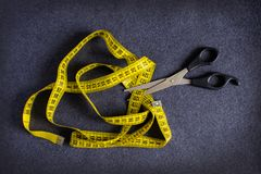 Tesouras pretas metálicas que cortam uma fita métrica amarela no CCB fotos de stock royalty free