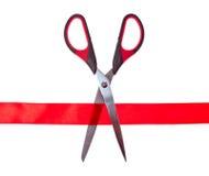 Tesouras que cortam através da fita vermelha Fotos de Stock