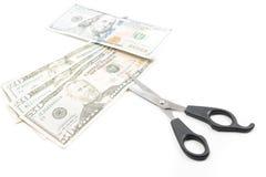 Tesouras que cortam contas de dinheiro do dólar, conceito do dinheiro das economias Fotos de Stock