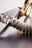 Tesouras que cortam o cabo de telefone Foto de Stock