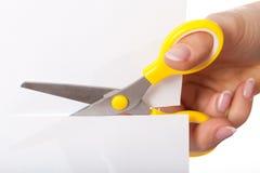 Tesouras que cortam o papel Fotografia de Stock Royalty Free