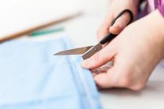 Tesouras que cortam o tecido imagem de stock royalty free