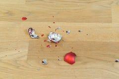 Tessons d'une boule cassée de Noël sur un plancher en bois Image stock