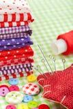 Tessuti variopinti, i bottoni, il cuscino del perno, il cilindro porta caratteri, bobina del filo - imposti per cucire Immagini Stock