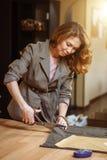Tessuto abbastanza messo a fuoco del vestito di taglio dello stilista della giovane donna in studio fotografie stock