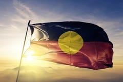 Tessuto aborigeno australiano del panno del tessuto della bandiera che ondeggia sulla nebbia superiore della foschia di alba immagini stock libere da diritti