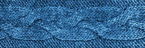 Tessuto blu dei lavori o indumenti a maglia con la treccia, struttura tricottata della lana del jersey immagine stock