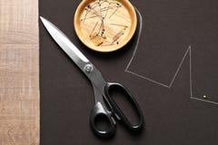 Tessuto con il modello del modello e gli strumenti di adattamento sulla tavola fotografia stock