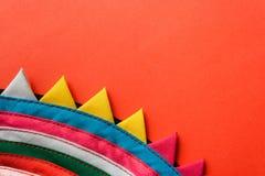 Tessuto cucito a strisce fatto a mano variopinto rotondo del primo piano con il bordo triangolare su fondo rosso fotografie stock libere da diritti
