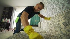 Tessuto di pulizia del sofà con un pulitore a vapore video d archivio