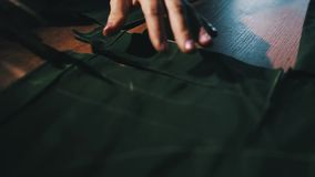 Tessuto di taglio del sarto facendo uso di grandi forbici o tagli come segue le marcature del gesso del modello, fine su del suo video d archivio
