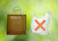 Tessuto e sacchetto di plastica facoltativo per preoccupazione dell'ambiente su fondo verde immagine stock