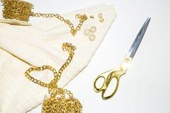 Tessuto ed accessori bianchi per la cucitrice, la catena dorata e le forbici dell'oro immagine stock