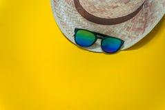 Tessuto ed occhiali da sole del cappello nel fondo giallo fotografia stock