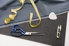 Tessuto, forbici e nastro di misurazione per sartoria Fotografie Stock