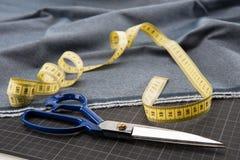 Tessuto, forbici e nastro di misurazione per sartoria Fotografia Stock