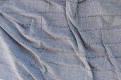 tessuto grigio sgualcito popolare su un copriletto grigio Struttura di tessuto sgualcito immagine stock libera da diritti