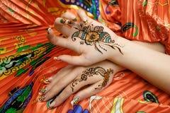 Tessuto luminoso arancio dell'immagine di mehendi delle mani di due donne con le pieghe Fotografia Stock Libera da Diritti