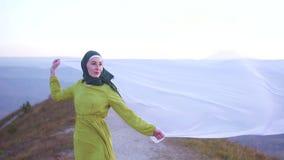 Tessuto nel vento nelle mani di bello modello musulmano della donna archivi video