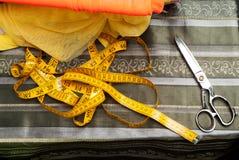 Tessuto o panno di cucito Tavola di lavoro di un sarto Strumenti del tessuto Forbici, nastri di misurazione Vista superiore Copi  immagine stock libera da diritti