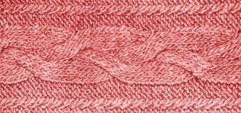 Tessuto rosso-chiaro dei lavori o indumenti a maglia con la treccia, struttura tricottata della lana del jersey immagini stock libere da diritti