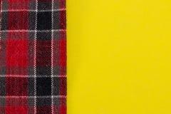 Tessuto rosso del plaid sul primo piano giallo del fondo Fotografie Stock