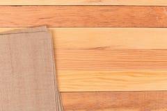 Tessuto sulla tavola di legno Delicatamente struttura di tela del tessuto tessuta marrone/ Immagini Stock