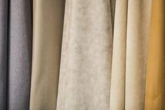 Tessuto sulle tende nel deposito Grandi campioni del tessuto della pelle scamosciata Fotografia Stock