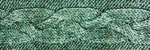 Tessuto verde dei lavori o indumenti a maglia con la treccia, struttura tricottata della lana del jersey fotografia stock