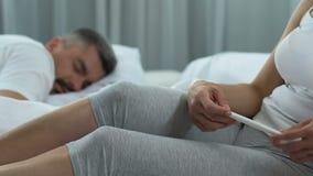Test di gravidanza della tenuta di signora, uomo che dorme vicino, facente pianificazione di gravidanza di decisione stock footage
