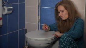 Test di gravidanza facente femminile con la pipetta sul coperchio del gabinetto Emozione triste negativa archivi video