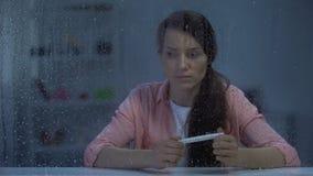 Test di gravidanza turbato della tenuta della donna con il risultato negativo, sterilità, giorno piovoso video d archivio