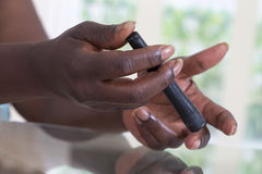 Test For Diabetes woman using lancelet on finger Stock Images