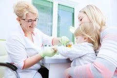 Test medicale o ricerca del sangue Prelievo del campione di sangue dal dito del bambino in ospedale fotografia stock