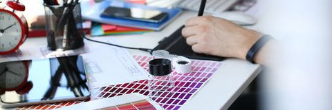 Test print paper page with colour test design fantail and magnifying glass. Lying at worktable for further promotion closeup royalty free stock photo